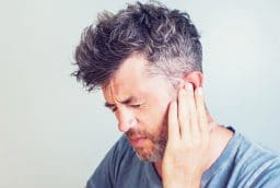 Man with earache is holding his aching ear