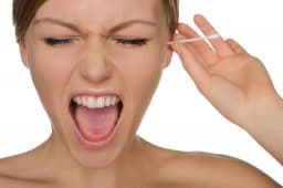 Woman screams while putting an ear swab in her ear