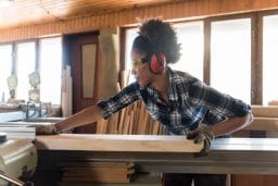 Woman using a wood splicer while wearing hearing protection